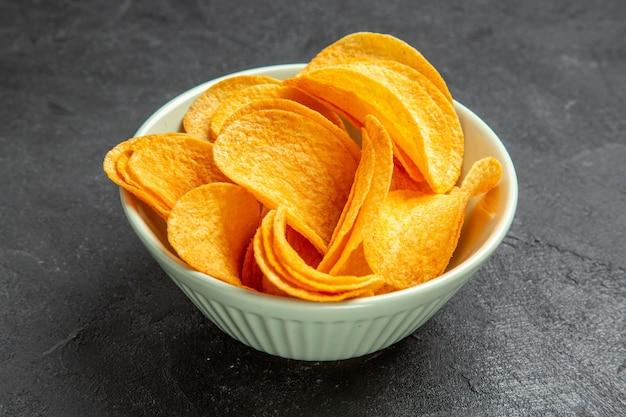 Vue de face des cips au fromage à l'intérieur de la plaque sur fond sombre photo de pomme de terre de cinéma de cinéma de collation