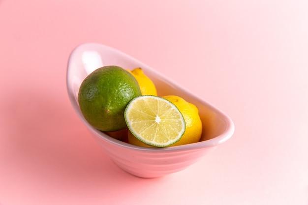 Vue de face de citrons frais avec de la chaux en tranches à l'intérieur de la plaque sur le mur rose