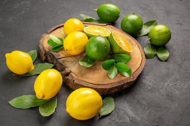 Vue de face citrons frais sur fond sombre fruits citron vert aigre-doux