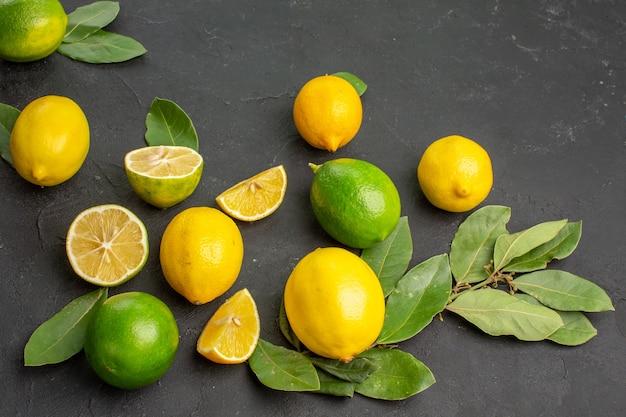 Vue de face de citrons frais fruits aigres sur le fond sombre