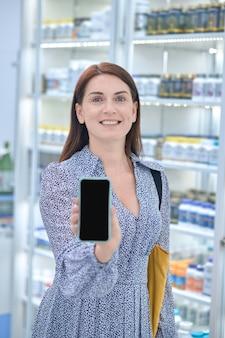 Vue de face d'une cliente de pharmacie d'âge moyen souriante et joyeuse démontrant son smartphone devant la caméra