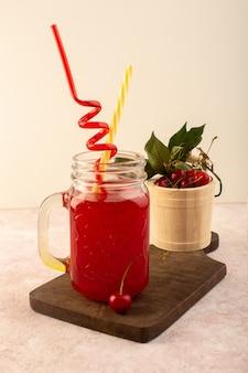 Une vue de face cocktail cerise rouge avec des pailles à l'intérieur peu de fraîcheur peut sur un bureau en bois et rose