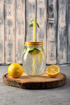 Une vue de face cocktail de citron boisson fraîche fraîche à l'intérieur de la coupe en verre citrons tranchés paille sur le bureau en bois et fond gris cocktail boisson fruit