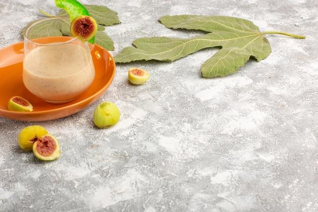 Vue de face cocktail frais à l'intérieur du verre avec des figues sur une surface blanche