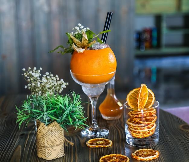 Vue de face cocktail rafraîchissant en orange avec décor de fleurs et tranches d'orange séchées