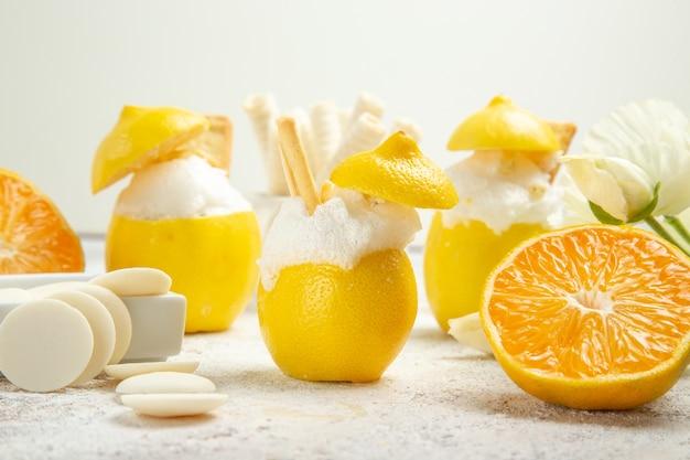 Vue de face des cocktails au citron avec des fruits sur un cocktail de jus de table blanc clair aux agrumes