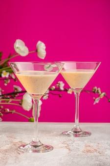 Vue de face des cocktails frais avec des fleurs sur une surface violette