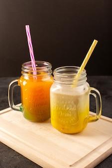 Une vue de face cocktails froids colorés à l'intérieur de boîtes en verre avec des pailles colorées sur le bureau crème en bois et sombre