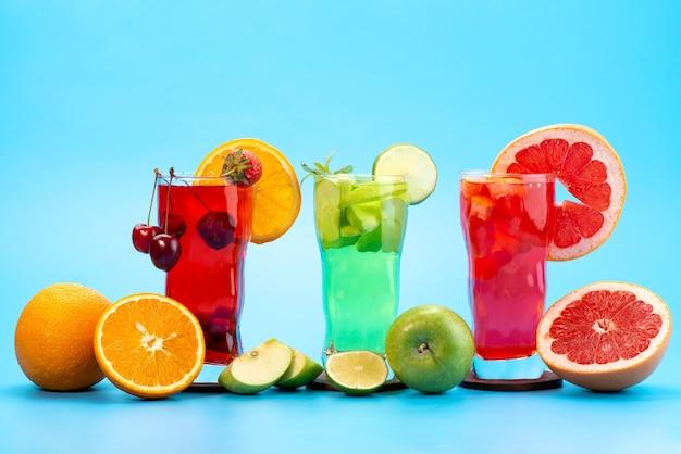 Une vue de face des cocktails de fruits frais avec des tranches de fruits frais refroidissement par glace sur bleu, boire du jus de fruits cocktail couleur de fruits