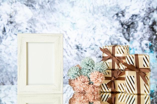 Vue de face des coffrets cadeaux de vacances cadre photo vide fleurs reflétées sur miroir