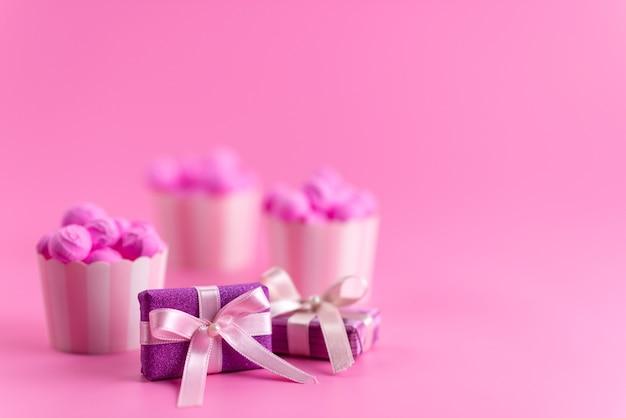 Une vue de face des coffrets cadeaux violets avec des bonbons roses sur un bureau rose