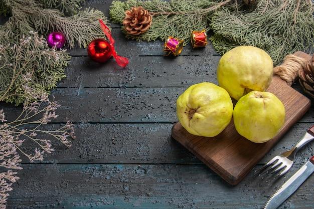 Vue de face coings mûrs frais fruits aigres sur un bureau rustique bleu foncé beaucoup de plantes fraîches arbre fruitier mûr