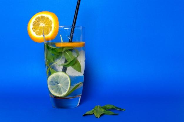 Une vue de face coktail froid frais avec des glaçons feuilles d'agrumes et de paille noire à l'intérieur de verre sur bleu