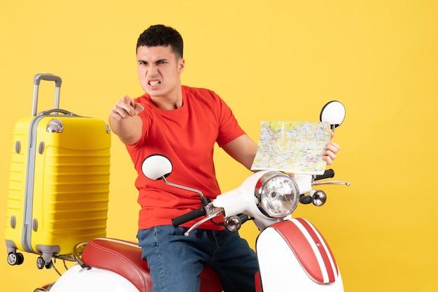 Vue de face en colère bel homme sur cyclomoteur tenant la carte pointant vers la caméra
