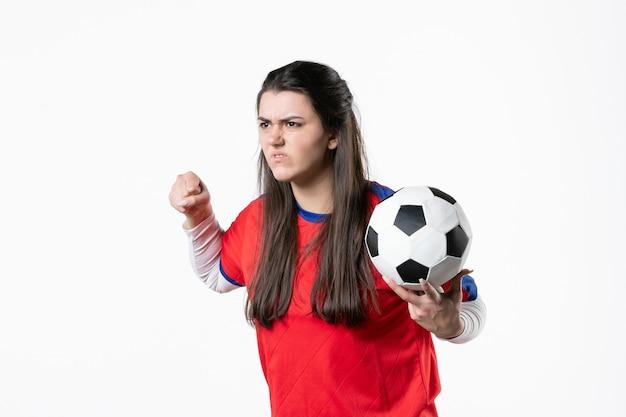 Vue de face en colère jeune femme en vêtements de sport avec ballon de foot