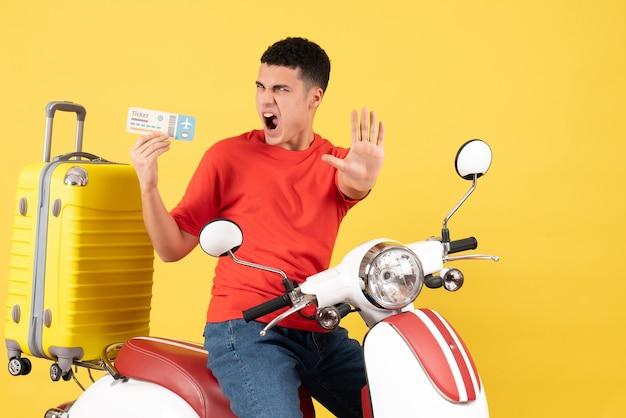Vue de face en colère jeune homme sur un cyclomoteur tenant un billet faisant panneau d'arrêt