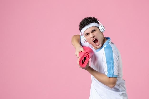 Vue de face en colère jeune homme en vêtements de sport avec tapis de yoga