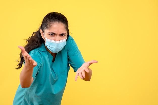 Vue de face en colère jolie femme médecin avec masque médical sur fond jaune