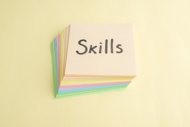 Vue de face compétences note écrite avec de petites notes de papier coloré sur fond clair