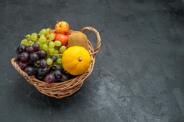 Vue de face composition de différents fruits frais et mûrs à l'intérieur du panier sur fond gris foncé fruits frais moelleux santé mûrs