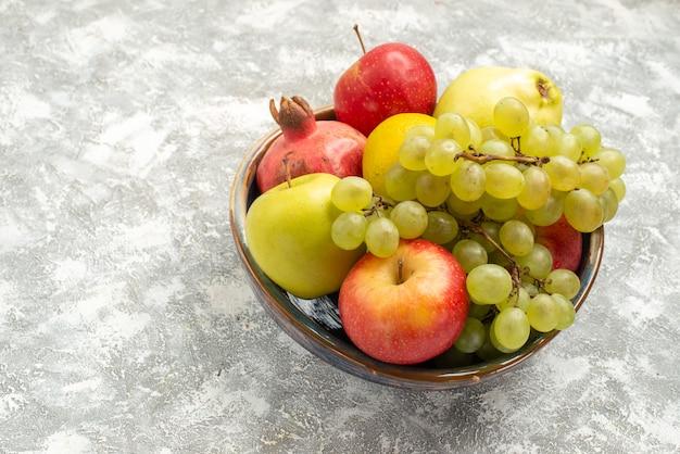 Vue de face de la composition de fruits frais pommes raisins et autres fruits sur un bureau blanc fruits frais mûrs vitamine couleur mûre