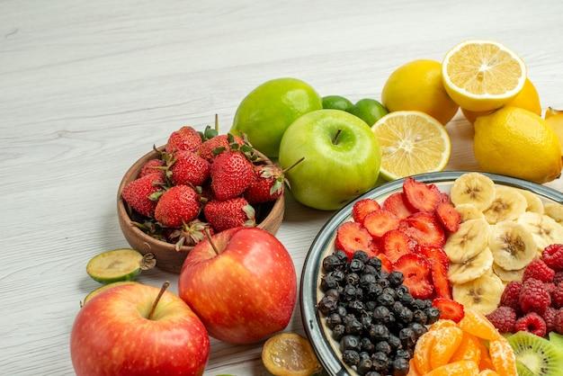 Vue de face composition de fruits avec salade de fruits en tranches sur surface blanche baies fruitées exotiques mûres photo moelleuse