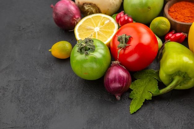 Vue de face composition de légumes frais avec assaisonnements sur surface sombre nourriture diététique vie saine repas salade