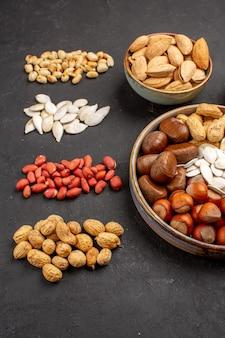 Vue de face de la composition de noix avec différentes noix fraîches sur une surface sombre