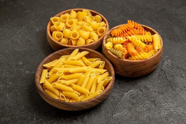 Vue de face de la composition des pâtes produits bruts à l'intérieur des assiettes sur un espace gris