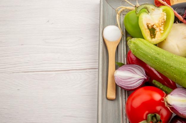 Vue de face composition végétale avec légumes verts et assaisonnements sur fond blanc couleur régime photo repas mûr vie saine
