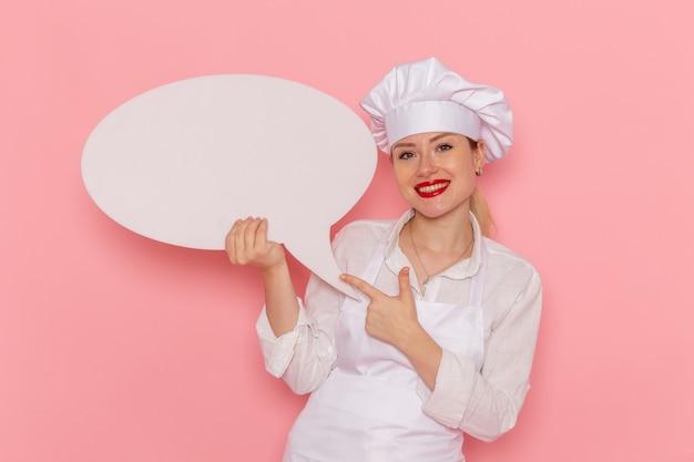 Vue de face confiseur femme en vêtements blancs tenant une pancarte blanche et souriant sur le mur rose confiserie pâtisserie travail travail