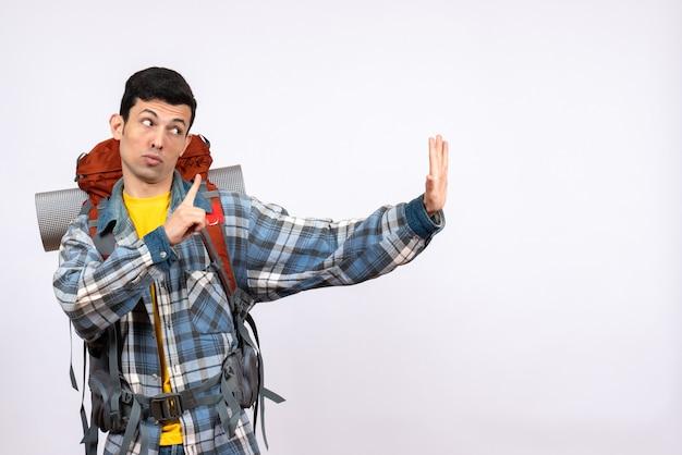 Vue de face confus jeune campeur avec sac à dos faisant panneau d'arrêt