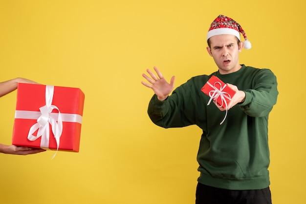 Vue de face confus jeune homme le cadeau en main féminine sur jaune