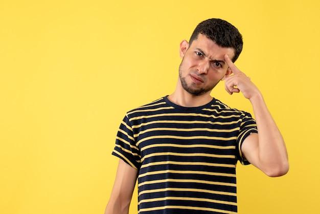 Vue de face confus jeune homme en t-shirt rayé noir et blanc fond isolé jaune