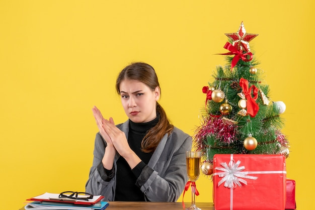 Vue de face confus jolie fille assise au bureau près de l'arbre de noël et des cadeaux cocktail
