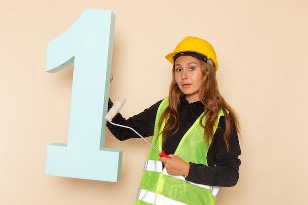 Vue de face constructeur féminin en casque jaune tenant la brosse et numéro un chiffre sur le mur blanc