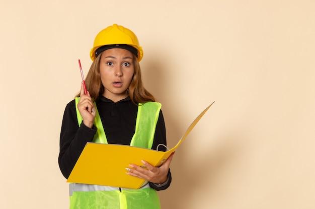 Vue de face constructeur féminin en casque jaune tenant un document jaune et un crayon sur un mur blanc