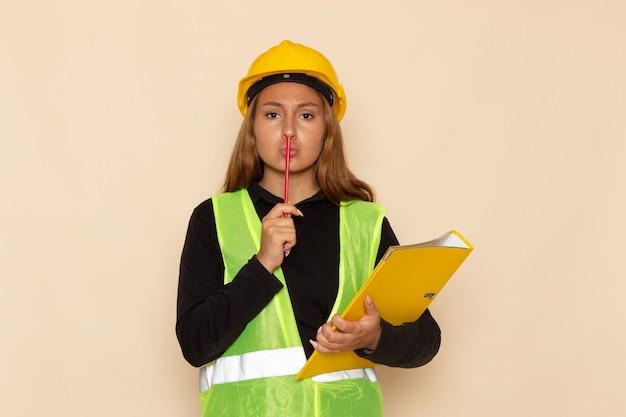 Vue de face constructeur féminin en casque jaune tenant un fichier jaune et un crayon sur la construction de constructeur de bureau blanc