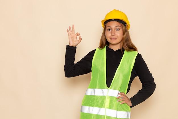 Vue de face constructeur féminin en chemise noire casque jaune montrant bien signe sur le mur blanc