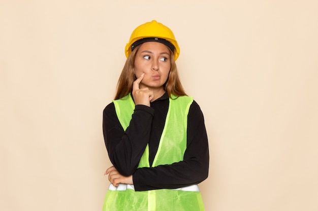 Vue de face constructeur féminin en chemise noire casque jaune posant la pensée sur le mur blanc