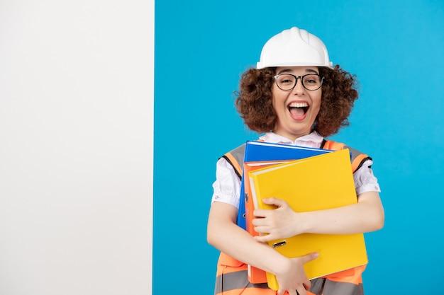 Vue de face constructeur féminin émotionnel en uniforme avec des documents sur bleu