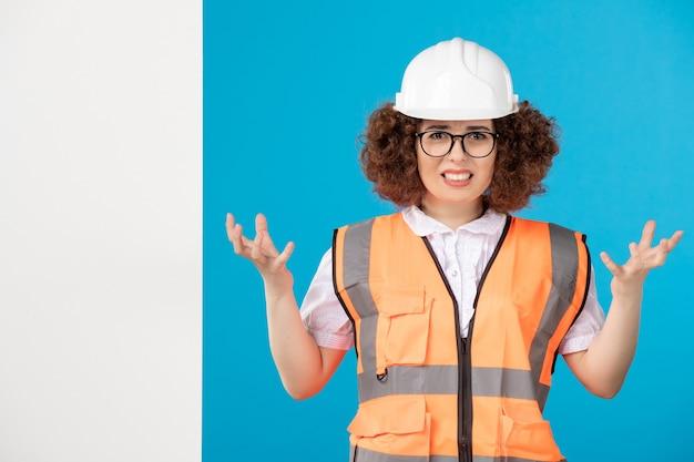 Vue de face constructeur féminin nerveux en uniforme sur bleu
