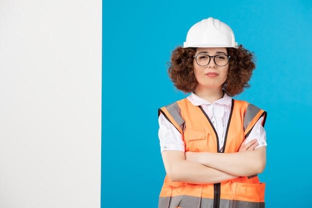 Vue de face constructeur féminin en uniforme sur le bleu
