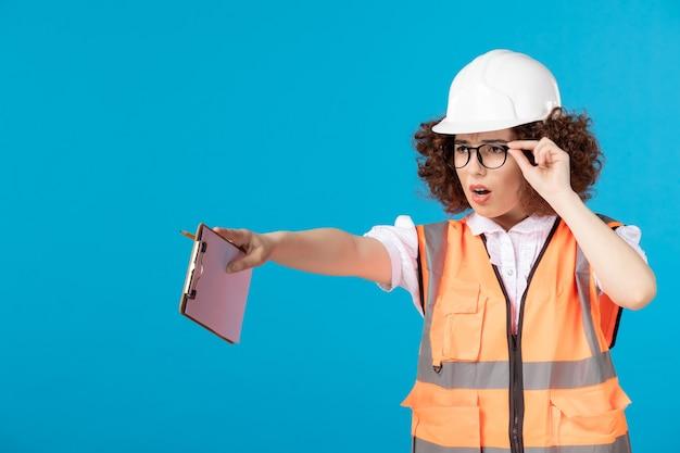 Vue de face constructeur féminin en uniforme avec note sur bleu