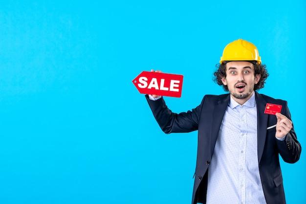 Vue de face constructeur masculin tenant une carte bancaire et vente écriture sur fond bleu conception maison travail architecture argent entreprise bâtiment