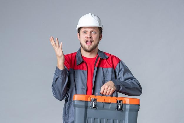 Vue de face constructeur masculin en uniforme et étui à outils tenant un casque sur fond gris