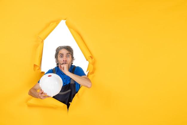 Vue de face constructeur masculin en uniforme sur fond jaune