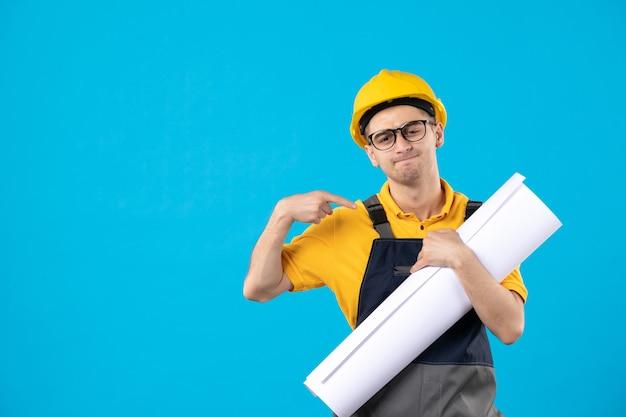 Vue de face constructeur masculin en uniforme jaune et casque sur bleu