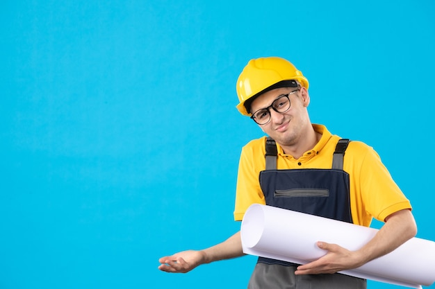 Vue de face constructeur masculin en uniforme jaune avec plan papier sur bleu