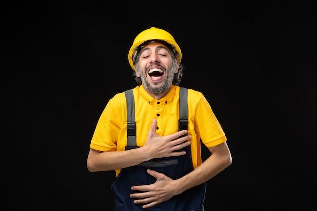 Vue de face constructeur masculin en uniforme sur un mur noir foncé